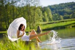 Source - femme romantique heureux s'asseyant par le lac Image stock