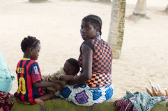 Source of independence. Abidjan, Cote d'Ivoire-29 August 2015: young woman with her two children rest in the shade of coconut palms. Peanut saleswoman in Stock Image