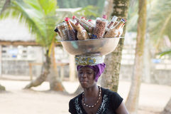 Source of independence. Abidjan, Ivory Coast - 29 August 2015: an African woman, bowl on her head filled with bottles full of roasted peanuts, walks on the beach Stock Photo