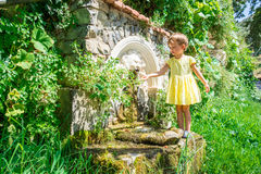 Source. Little girl in yellow dress washes at source Royalty Free Stock Image
