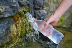 Source of spring water bottle filling holding hand Stock Photos