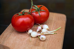 Source of vitamins garlic and tomatoes. Two tomatoes and young garlic on wooden cutting Board Stock Images