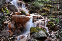 Sources with ferrous impurities flowing over large stones. Landscape photography. Sources with ferrous impurities flowing over large stones Stock Photo