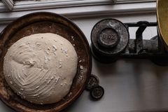 Sourdough bread dough ready for the oven, with weights and weighing scales royalty free stock image