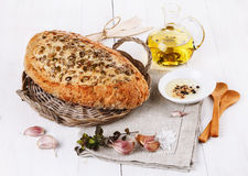 Sourdough bread with seeds, garlic and oil over rustic backgroun Royalty Free Stock Photography