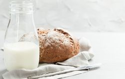 Sourdough craft flax bread with bottle of milk on light gray background stock image