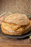 Sourdough homemade round white wheat bread close up. Sourdough homemade round white wheat bread with slices on table close up royalty free stock photography