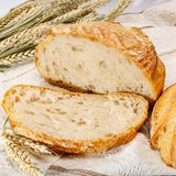 Sourdough homemade round white wheat bread with slices close up. Sourdough homemade round white wheat bread with slices on table close up royalty free stock image