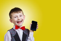 Souriant beau petit garçon heureux et joyeux tenant le téléphone portable Photographie stock libre de droits