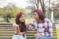 Souriant deux amis parlant en parc Image stock