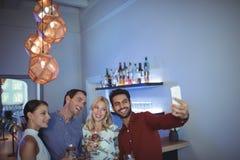 Souriant deux couples posant ensemble tout en parlant un selfie Photo stock