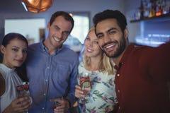 Souriant deux couples tenant des verres de cocktail Images stock