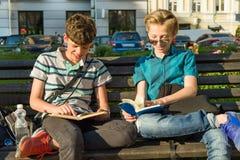 Souriant deux livres de lecture d'écoliers se reposant sur un banc dans la ville Images stock