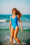 Souriant, femme heureuse dans le bikini espiègle sur la plage tropicale de paradis avec l'océan photo stock
