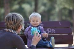 Souriant, mangeant le bébé avec sa mère photographie stock