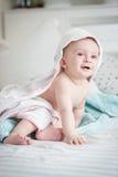 Souriant 9 mois de bébé garçon s'asseyant sur le lit couvert en serviette af Photos stock