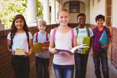 Souriant peu d'enfants d'école dans le couloir d'école Photographie stock