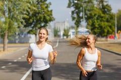 Souriant, positif, jolies filles courant sur un fond de parc Sports avec le concept d'amis Image stock