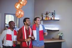 Souriant trois amis ayant la bière tout en regardant la rencontre Photos libres de droits