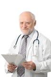 Sourire aîné de papiers de fixation de docteur Images stock