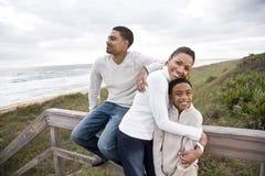 Sourire afro-américain de famille, étreignant à la plage photographie stock libre de droits