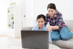 Sourire amis assez féminins à l'aide de l'ordinateur nomade Images libres de droits