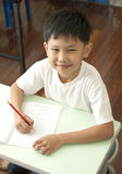 Sourire asiatique de gosse dans la chambre de classe Photo stock