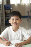 Sourire asiatique de gosse dans la chambre de classe Photographie stock