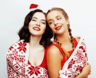 Sourire assez heureux de jeunes blond et amies de femme de brune Noël dans le chapeau rouge de Santa et des vacances décorées Photos libres de droits