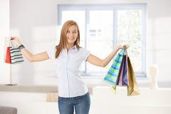 Sourire attrayant de sacs à provisions de fixation de fille Photos stock