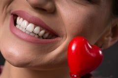Sourire attrayant et dents blanches avec le coeur rouge image stock