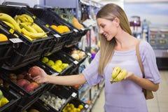 Sourire bananes de achat de femme assez blonde image libre de droits