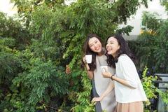 Sourire bien habillé d'amies heureuses de jeunes femmes tout en se tenant à Photographie stock libre de droits