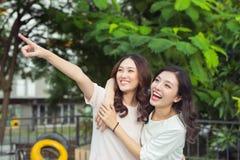 Sourire bien habillé d'amies heureuses de jeunes femmes tout en se tenant à Images libres de droits