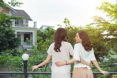 Sourire bien habillé d'amies heureuses de jeunes femmes tout en se tenant à Photographie stock