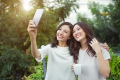 Sourire bien habillé d'amies heureuses de jeunes femmes tout en se tenant à Image stock