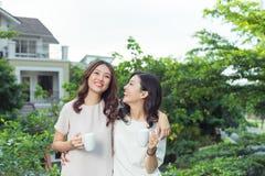 Sourire bien habillé d'amies heureuses de jeunes femmes tout en se tenant à Photos libres de droits