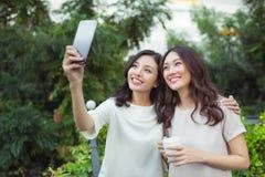 Sourire bien habillé d'amies heureuses de jeunes femmes tout en se tenant à Photo libre de droits