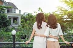 Sourire bien habillé d'amies heureuses de jeunes femmes tout en se tenant à Images stock