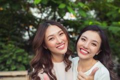 Sourire bien habillé d'amies heureuses de jeunes femmes tout en se tenant ensemble Photos stock