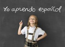 Sourire blond junior doux d'écolière heureux chez les enfants apprenant le concept de langue espagnole et d'éducation Photo stock