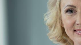 Sourire blond supérieur gai dans l'appareil-photo, clinique de chirurgie plastique, plan rapproché banque de vidéos