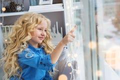 Sourire contacts de fille assez petite à la fenêtre photos libres de droits