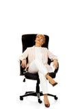 Sourire détendant la femme pluse âgé d'affaires s'asseyant sur le fauteuil photographie stock libre de droits