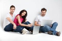 Sourire d'amis heureux avec des ordinateurs portatifs Photographie stock libre de droits