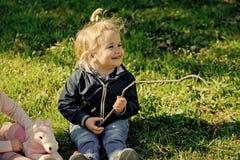 Sourire d'enfant de garçon avec le bâton sur l'herbe verte photos libres de droits
