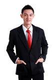 Sourire d'homme d'affaires portant une cravate rouge et un costume noir sur le CCB blanc Photos stock
