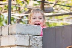 Sourire de cinq ans de fille regardé par derrière le mur Photo stock