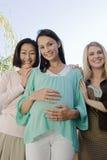 Sourire de femme enceinte et d'amis Images libres de droits