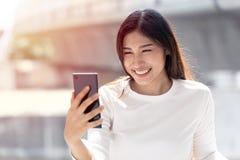 Sourire de fille semblant l'écran intelligent de appeler de téléphone pour le selfie ou l'appel visuel photographie stock